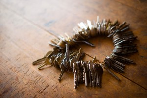Many old keys on a well used old wooden desk.